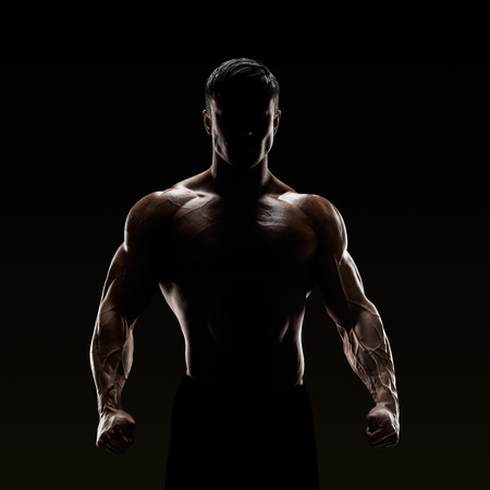 champion: Silhouette of a strong fighter. Confident young fitness man with strong hands and clenched fists.