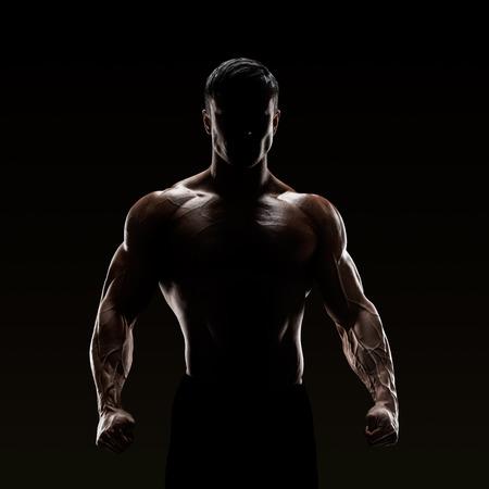 niño sin camisa: Silueta de un peleador fuerte. Hombre confidente joven de la aptitud con las manos fuertes y los puños apretados.
