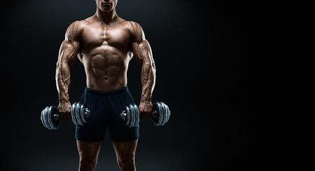 bodybuilder: Poder guapo hombre atlético culturista haciendo ejercicios con mancuernas. Musculoso cuerpo fitness en el fondo oscuro. Foto en blanco y negro con copia espacio