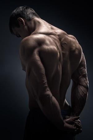 Handsome muscular male model bodybuilder preparing for fitness training turned back. Studio shot on black background.