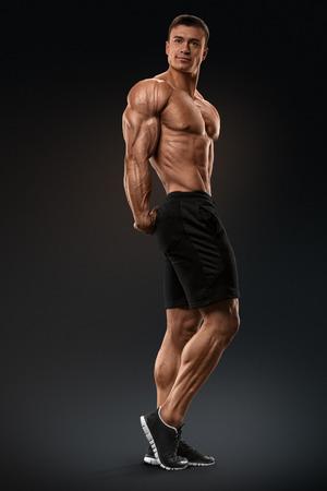 Gespierd en fit bodybuilder fitness mannelijk model poseren op een zwarte achtergrond. Sterk en knappe jonge man aan te tonen zijn gespierde torso en biceps. Lichaam van gespierde man met een grote lichaamsbouw Stockfoto