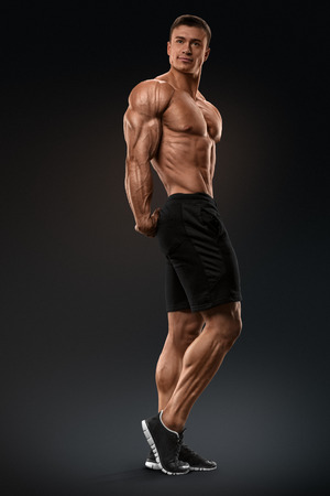Muscular and fit bodybuilder fitness male model posing over black background. Strong and handsome young man demonstrate his muscular torso and biceps. Body of muscular male with great physique
