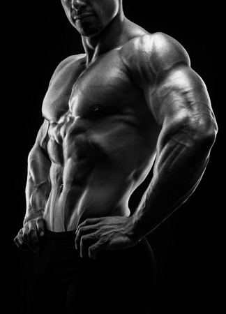 Muscular and fit young bodybuilder fitness male model posing over black background. Black and white photo.