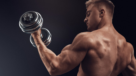 Closeup of a handsome power athletic man bodybuilder doing exercises with dumbbell. Fitness muscular body on dark background.
