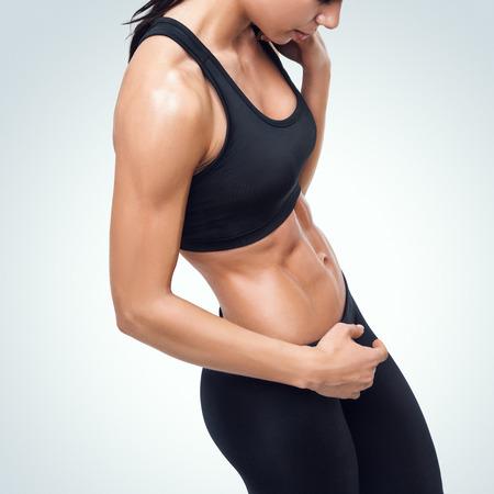 Sportieve jonge vrouw die een onderbreking in een sportschool toont haar goed getraind lichaam. Stockfoto