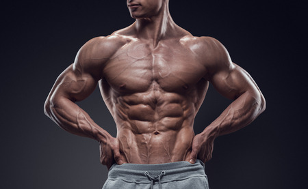 six: Handsome power athletic young man with great physique. Strong bodybuilder with six pack perfect abs shoulders biceps triceps and chest. Image have clipping path
