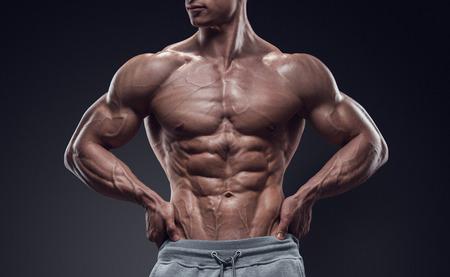 uomini belli: Potere Handsome giovane atletico con grande fisico. Forte bodybuilder con six pack abs perfetti spalle bicipiti tricipiti e petto. Immagine ha tracciato di ritaglio