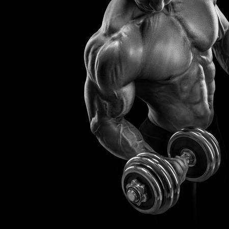 musculoso: Primer plano de un poder guapo chico atlético culturista masculino haciendo ejercicios con mancuernas. Musculoso cuerpo fitness en el fondo oscuro. Foto de archivo