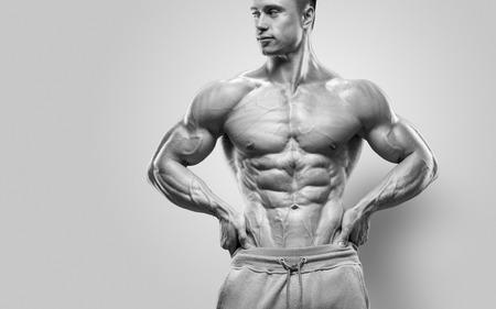 Handsome sportliche Leistung junger Mann mit großen Körperbau. Starke Bodybuilder mit Sixpack perfekte abs Schultern Bizeps Trizeps und Brust. Studio Schuss auf weißem Hintergrund Standard-Bild