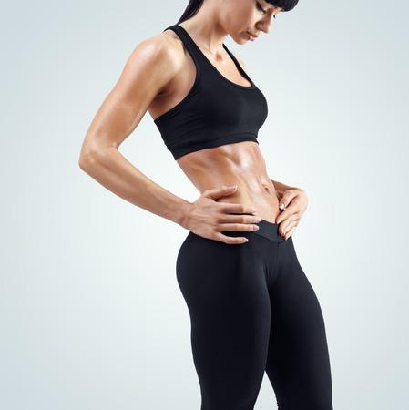 Mulher desportiva da aptidão que mostra seu corpo bem treinado isolado no fundo branco. Forte abs mostrando.