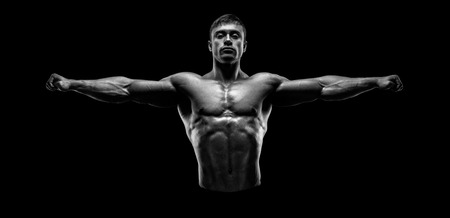 Handsome muscular bodybuilder posing and keeping arms outstretched. Muscular and fit young bodybuilder posing raising his hands on black background. Black and white photo. Stock Photo