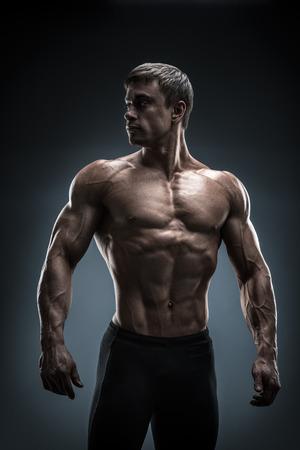 Overweldigende gespierde jongemannen bodybuilder stellen en op zoek achter. Studio opname op zwarte achtergrond.