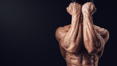 musculo: Dos Manos Eléctricas delante de la cara. Primer plano de una puños man39s y los abdominales. Man39s brazo fuerte con los músculos y las venas. Foto de archivo