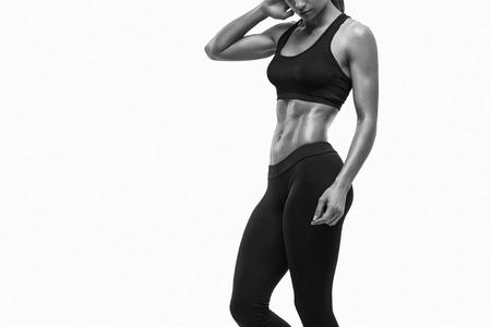 健身: 健身運動的女人呈現出她的訓練有素的身體。強大的腹肌展示。 版權商用圖片