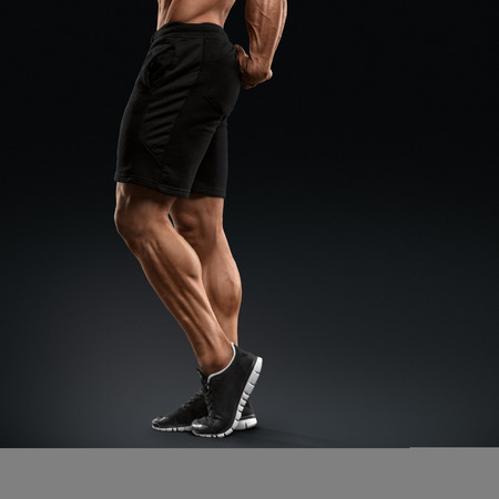Modelo masculino de la aptitud culturista muscular y en forma posando sobre fondo negro. Hombre joven fuerte y apuesto demostrar su torso musculoso y bíceps. Cuerpo de hombre musculoso con gran físico Foto de archivo - 41421831