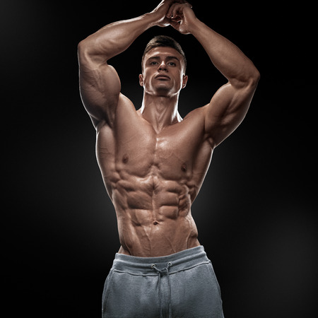 Strong athletic man fitness model torso showing six pack abs. Isolated on black background.