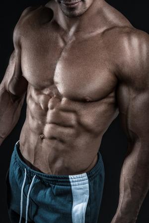 sin camisa: Modelo masculino muscular joven y en forma física culturista posando sobre fondo negro. Estudio disparó sobre fondo negro.