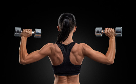 Fitness sporty woman in training pumping up muscles of the back and hands with dumbbells 스톡 콘텐츠
