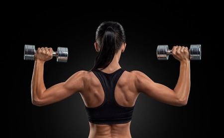 fitness: Mujer de la aptitud deportiva en el entrenamiento de bombeo de los músculos de la espalda y las manos con mancuernas
