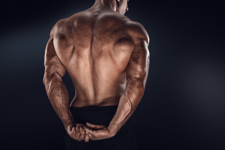 attractive male: Handsome power athletic man showing his back. Strong bodybuilder with shoulders biceps triceps and chest