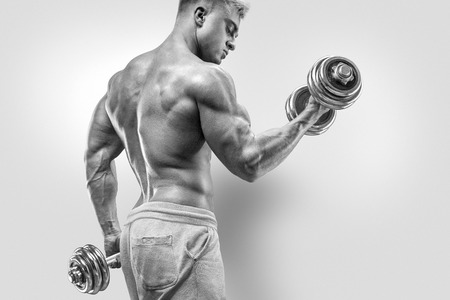attractive male: Handsome power athletic man in training pumping up muscles with dumbbell. Strong bodybuilder with six pack perfect abs shoulders biceps triceps and chest. Image with clipping path