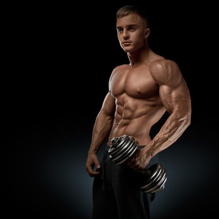musculoso: Poder guapo hombre atlético con pesas con confianza mirando hacia adelante. Culturista fuerte con six pack abs hombros perfecta bíceps tríceps y pecho