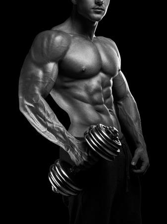 Knap macht atletische man met een halter met vertrouwen naar uit. Sterke bodybuilder met zes pack abs perfecte schouders biceps triceps en borst