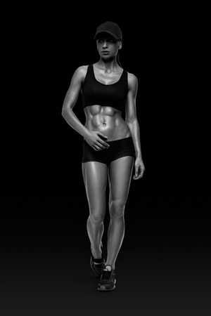 Fitness sporty woman walking on white background. Strong abs showing. Banque d'images