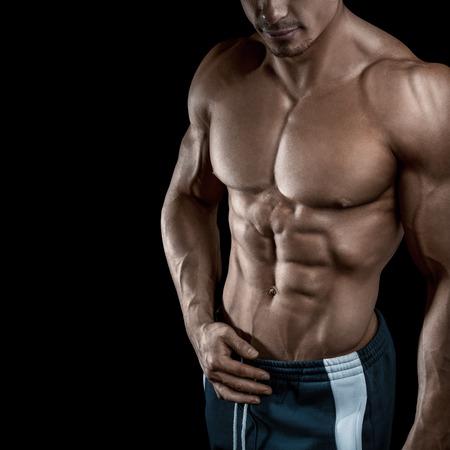 筋肉とフィットの若いボディビルダー フィットネスの男性モデルは、黒背景にポーズします。スタジオは、黒い背景で撮影。