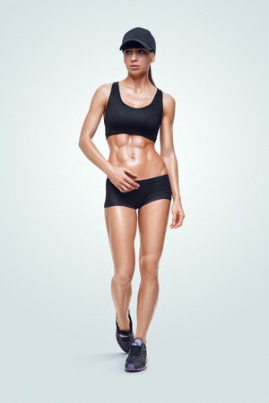Fitness sporty woman walking on white background. Strong abs showing. 스톡 콘텐츠