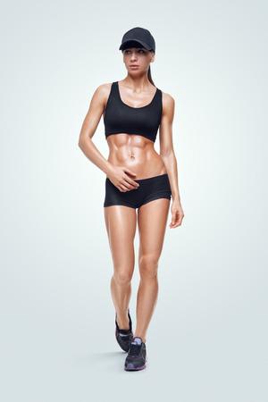 Fitness sportieve vrouw lopen op een witte achtergrond. Sterke abs tonen.