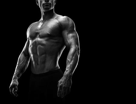Stattlicher muskulöser Bodybuilder Vorbereitung für Fitness-Training. Schwarzweiss-Foto mit Kopie Raum