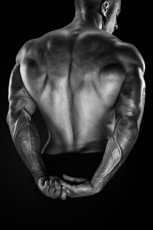 Handsome power athletic man showing his back. Strong bodybuilder with shoulders biceps triceps and chest