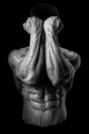 abs: Two Power Hands in Front of Face. Closeup of a man39s fists and abs. Strong man39s arm with muscles and veins.