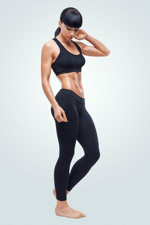 Fitness sportieve vrouw die haar goed getraind lichaam. Sterke buikspieren tonen. Stockfoto