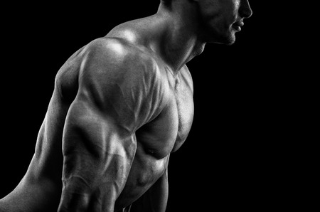 health club: Handsome muscular bodybuilder preparing for fitness training confidently looking forward. Studio shot on black background. Black and white photo.