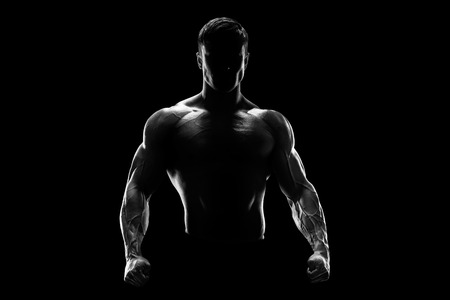 Silhouette of a strong fighter. Confident young fitness man with strong hands and clenched fists. Dramatic light.