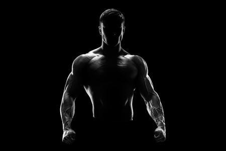 Silhouette di un combattente forte. Fiducioso giovane fitness con mani forti e pugni chiusi. Luce drammatica. Archivio Fotografico - 41422010