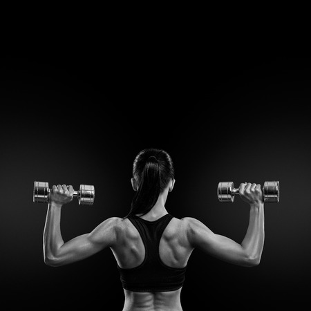 Fitness sporty woman in training pumping up muscles of the back and hands with dumbbells. Black and white concept image. Stock Photo