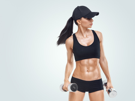 Fitness sporty woman in training pumping up muscles with dumbbells isolated on white background. Strong abs showing. Image with copyspace for text.