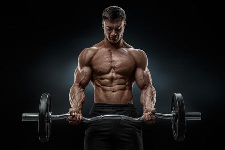 ropa deportiva: Primer retrato de un entrenamiento muscular hombre con mancuerna en el gimnasio. Culturista hombre atlético Brutal con six pack abs perfectos hombros bíceps tríceps y pecho. Pesas Peso Muerto entrenamiento.