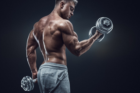 in the back: Handsome power athletic man in training pumping up muscles with dumbbells. Strong bodybuilder with six pack perfect abs shoulders biceps triceps and chest.