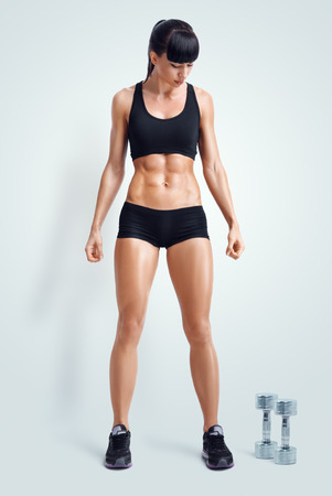 Fit female athlete in activewear ready to doing exercise with dumbbells. Strong abs showing. Image with clipping path. Banque d'images