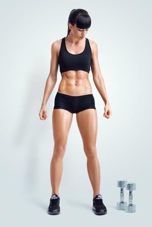 Fit vrouwelijke atleet in activewear klaar om te doen van oefeningen met halters. Sterke buikspieren tonen. Afbeelding met het knippen van weg. Stockfoto