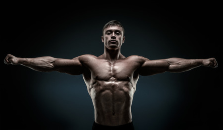 pesas: Hermoso que presenta culturista muscular y manteniendo los brazos extendidos. joven fisicoculturista muscular y del ajuste que presenta levantando las manos sobre fondo negro. Foto de archivo