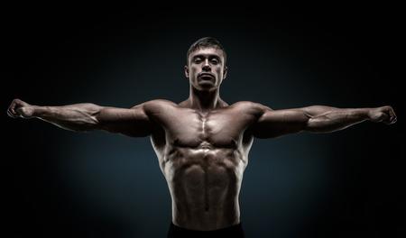 Stattlicher muskulöser Bodybuilder posiert und halten die Arme ausgestreckt. Muskulös und Fit jungen Bodybuilder posiert hob die Hände auf schwarzem Hintergrund.
