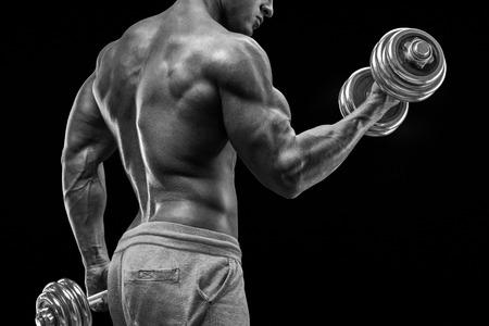 silueta hombre: Poder guapo hombre atlético en el entrenamiento el bombeo de los músculos con pesas. Culturista fuerte con seis paquetes perfectos hombros abs bíceps tríceps y pecho. Foto de archivo