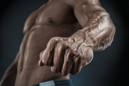 musculoso: Culturista muscular hermoso demuestra el puño y la vena vasos sanguíneos. Estudio disparó sobre fondo negro.