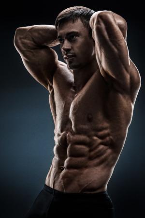 cuerpo hombre: Culturista masculino sin camisa Potente posando sobre fondo negro Foto de archivo