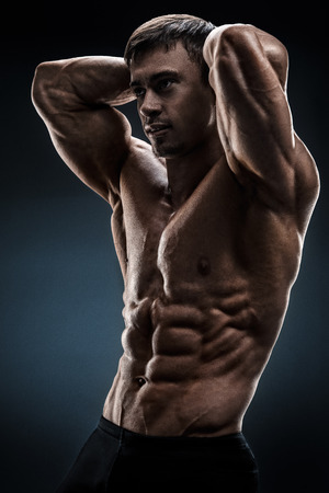 shirtless male: Powerful shirtless male bodybuilder posing over black background